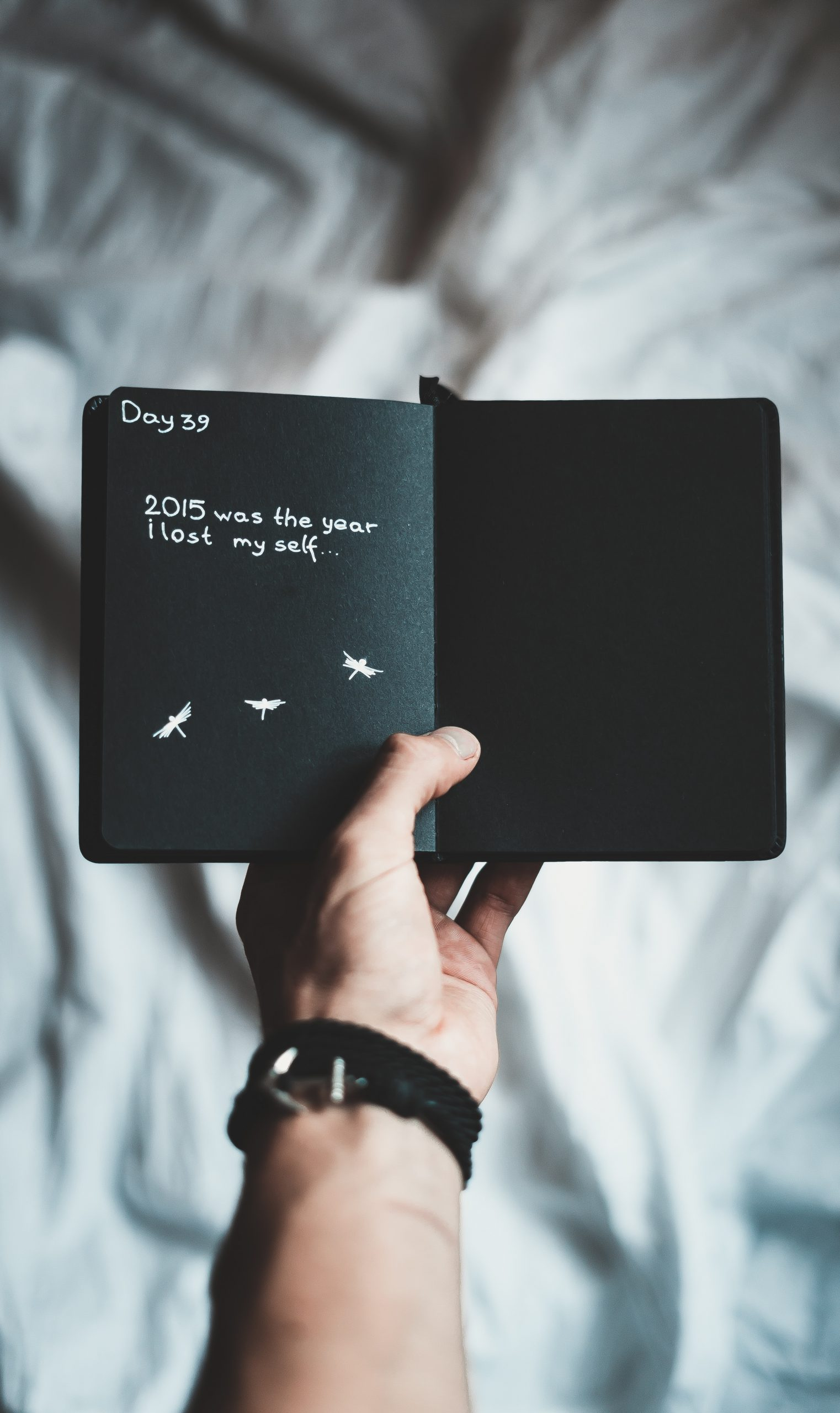 person holding black notebook